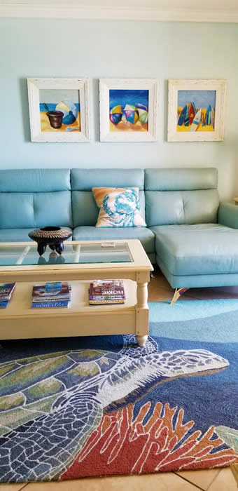 bright colored area rug in living room brings in the colors of the artwork